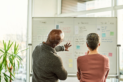 Buy stock photo Cropped shot of two unrecognizable businesspeople standing together and using a white board during a discussion in the office