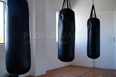 Buy stock photo Cropped shot of three punching bags hanging in a gym