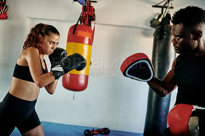 Buy stock photo Cropped shot of an attractive young female boxer sparring with her personal trainer in a gym