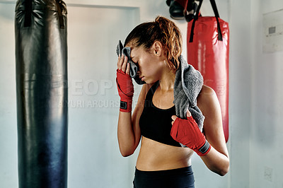 Buy stock photo Cropped shot of an attractive young female boxer wiping her face with a towel in a gym
