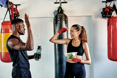 Buy stock photo Cropped shot of an attractive young female boxer high fiving her fitness coach during their lunch break in a gym