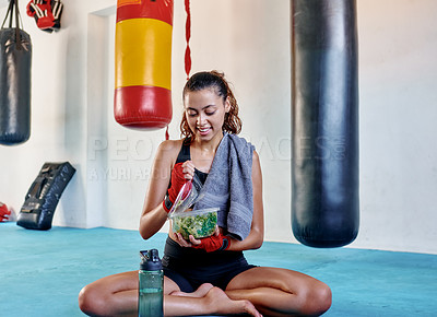Buy stock photo Full length shot of an attractive young female boxer having fresh vegetable salad for lunch in a gym