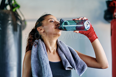 Buy stock photo Cropped shot of an attractive young female boxer drinking water in a gym