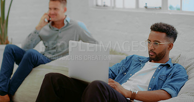 Buy stock photo Shot of a young businessman using a laptop while relaxing on a beanbag in a modern office