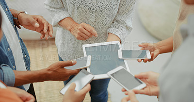 Buy stock photo Cropped shot of a group of businesspeople using their smart devices together at work