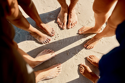 Buy stock photo Cropped shot of a group of friends standing barefoot on the beach