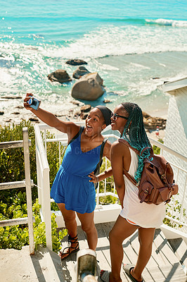 Buy stock photo Shot of two female friends taking a selfie while posing outdoors