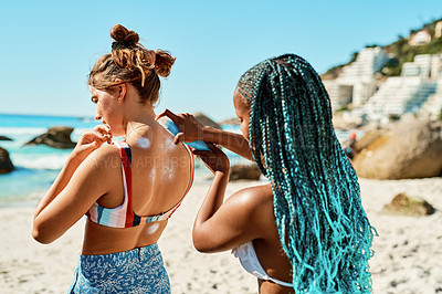 Buy stock photo Shot of a young woman applying sunscreen to her friend's back on the beach