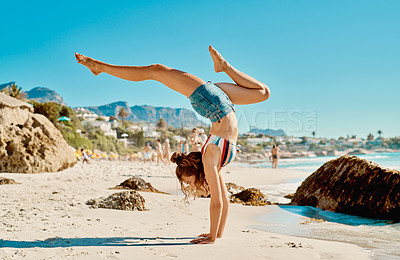 Buy stock photo Shot of a young woman doing handstands on the beach
