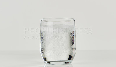 Buy stock photo Cropped shot of a glass of carbonated water sitting on the tabletop of an empty kitchen