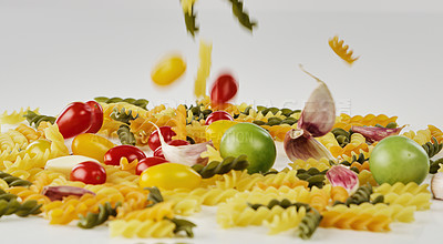 Buy stock photo Cropped shot of pasta, garlic cloves and tomatoes falling onto the tabletop of an empty kitchen