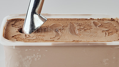 Buy stock photo Cropped shot of a metal scoop in a tub of chocolate ice cream on the tabletop of an empty kitchen