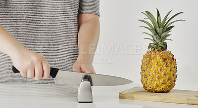 Buy stock photo Cropped shot of an unrecognizable woman sharpening a knife before cutting into a pineapple in the kitchen