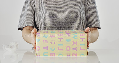 Buy stock photo Cropped shot of an unrecognizable woman holding a neatly wrapped gift box in the studio