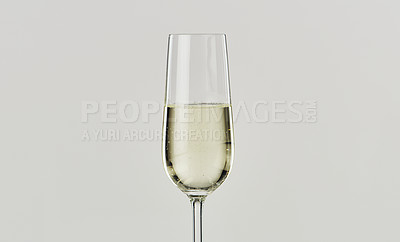 Buy stock photo Cropped shot of a glass of champagne against a gray background in the studio