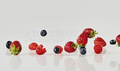 Buy stock photo Cropped shot of an assortment of fresh berries falling onto the tabletop in an empty kitchen