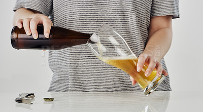 Buy stock photo Cropped shot of an unrecognizable woman standing and pouring a bottle of beer into a glass in the studio