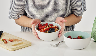 Buy stock photo Cropped shot of an unrecognizable woman preparing a bowl of oats and berries for breakfast in the studio