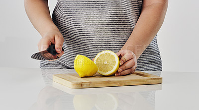 Buy stock photo Cropped shot of an unrecognizable woman cutting lemon on a wooden board the studio during the day