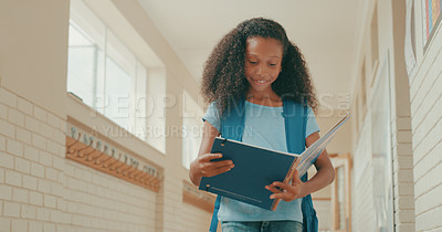 Buy stock photo Shot of a young girl walking down a school hall and reading a book