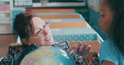 Buy stock photo Shot of a teacher showing her student a globe of the world