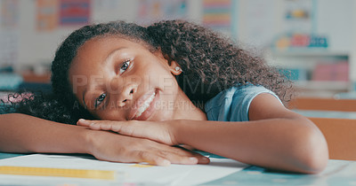 Buy stock photo Shot of a happy young girl sitting at her desk in a classroom