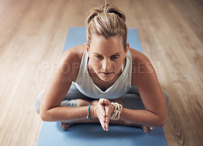 Buy stock photo Cropped shot of an attractive young woman sitting alone on a yoga mat and holding a yoga pose