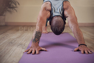 Buy stock photo Cropped shot of an unrecognizable man holding a downward facing dog pose during an indoor yoga session alone