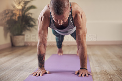 Buy stock photo Cropped shot of a handsome young man holding a high plank pose during an indoor yoga session alone