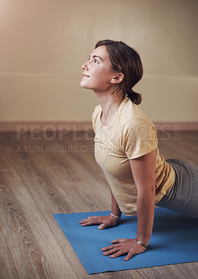 Buy stock photo Cropped shot of an attractive young woman holding an upward facing dog pose during an indoor yoga session alone