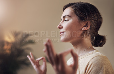 Buy stock photo Cropped shot of an attractive young woman sitting alone and meditating indoors