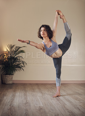 Buy stock photo Full length shot of an attractive young woman holding a dancer's pose while doing yoga alone indoors