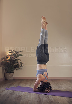 Buy stock photo Full length shot of an unrecognizable woman holding an elbow stand during an indoor yoga session alone