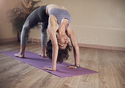 Buy stock photo Full length shot of an attractive young woman holding an upward facing bow pose during an indoor yoga session alone