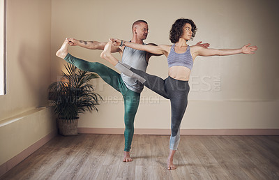 Buy stock photo Full length shot of two young yogis standing together and holding a yoga pose during an indoor session indoors