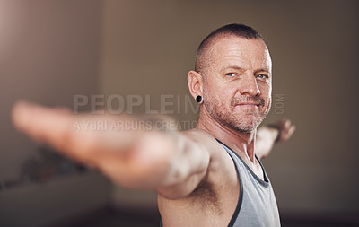 Buy stock photo Cropped shot of a handsome young man standing and holding a warrior two pose during an indoor session alone