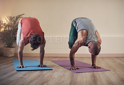 Buy stock photo Full length shot of two unrecognizable men holding a crane pose during an indoor yoga session together