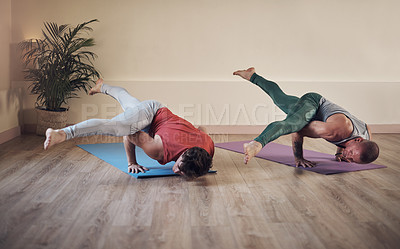 Buy stock photo Full length shot of two young men holding an extended side crow pose during an indoor yoga session together