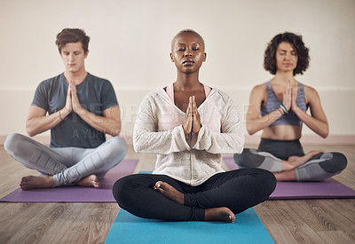 Buy stock photo Full length shot of a diverse group of yogis sitting together and meditating after an indoor yoga session