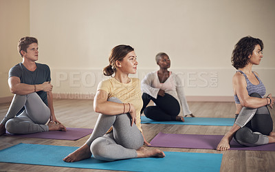 Buy stock photo Full length shot of a diverse group of yogis holding a spinal half twist pose during an indoor yoga session