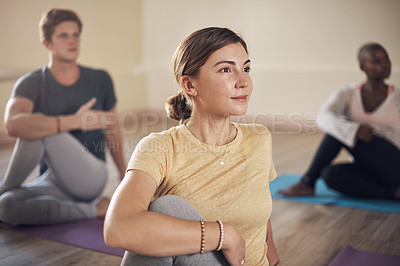 Buy stock photo Cropped shot of a diverse group of yogis holding a spinal half twist pose during an indoor yoga session
