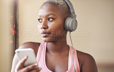 Buy stock photo Cropped shot of an attractive young woman sitting and wearing headphones while listening to music through her cellphone