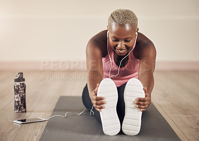Buy stock photo Full length shot of an attractive young woman sitting alone and stretching before a workout indoors