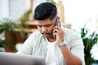 Buy stock photo Shot of a young businessman using a laptop and smartphone in a modern office