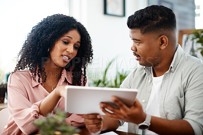 Buy stock photo Shot of a young businessman and businesswoman using a digital tablet in a modern office