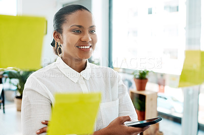 Buy stock photo Shot of a young businesswoman using a smartphone while having a brainstorming session in a modern office