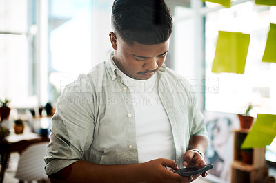 Buy stock photo Shot of a young businessman using a smartphone while having a brainstorming session in a modern office