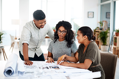 Buy stock photo Shot of a group of young businesspeople working on a blueprint in a modern office