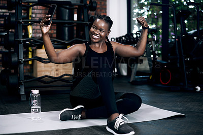 Buy stock photo Full length shot of an attractive young female athlete flexing her biceps while sitting on her towel in the gym