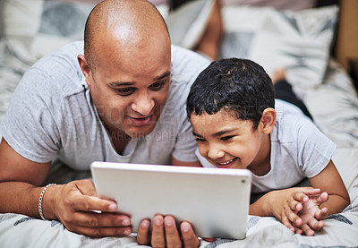 Buy stock photo Cropped shot of a cheerful young man and his son watching videos on a digital tablet while hanging out on a bed at home during the day
